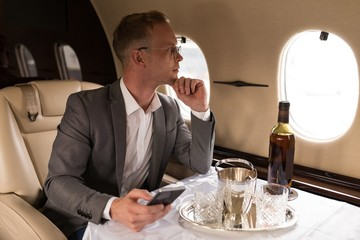 Thoughtful businessman looking through window while sitting in private jet