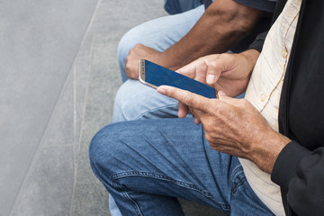 older man holding a cell phone reviewing the photos he has taken recently