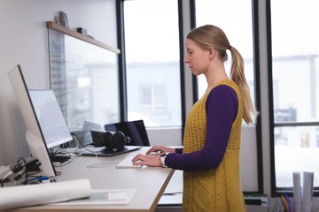 Young businesswoman working on desktop computer in office