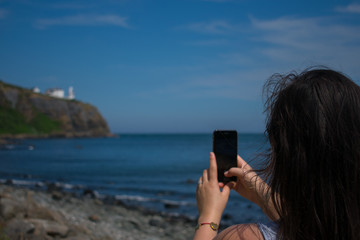 back view of woman with dark hair taking photo or picture of sea coast in northern ireland on her smartphone