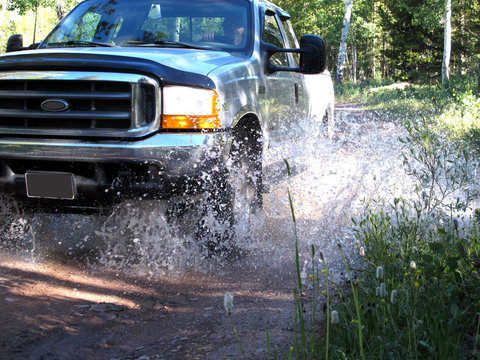 Silver Four Wheel Drive Pick Up Truck Splashing Through Mountain Stream Bed