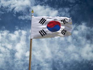South Korea flag Silk waving flag of South Korea made transparent fabric with wooden flagpole gold spear on background blue sky white smoke clouds real retro photo Taegukgi taeguk 3d illustration