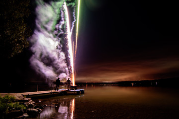 Fireworks on a dock over the water with smoke and lake horizon