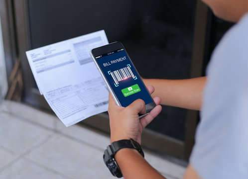 Mobile bill payment barcode scan concept.Man hands using mobile phone and holding bills