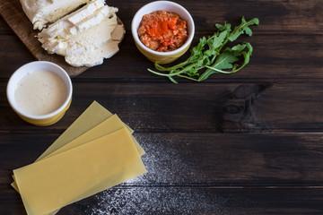 Process of preparing lasagna. Traditional italian food. Raw lasagna dough, mozarella cheese, bolognese sauce, bechamel sauce, arugula on wooden background.