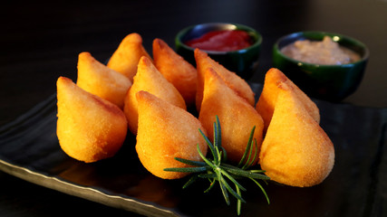 Coxinhas Brazilian snack stuffed with chicken on dark background. Traditional party food.