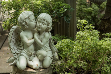 Cute kissed couple cupid in garden