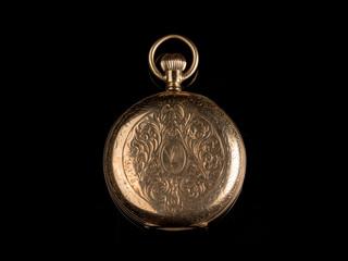Old golden pocket watch on a black reflective surface