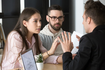 Angry millennial couple argue with realtor or broker dissatisfied with house project, spouses dispute with contractor or architect blaming for construction problems, having complaints about home plan