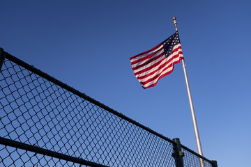 American Flog Red White And Blue Above A Fence