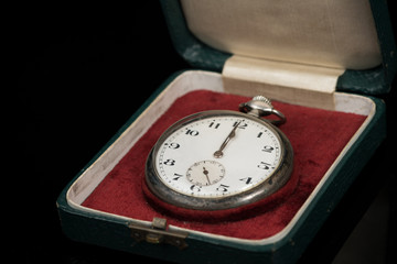 Old used pocket watch in a case on a black reflective surface