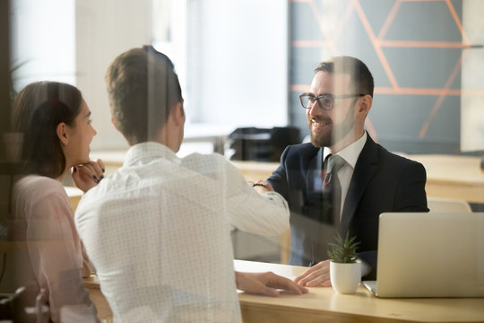 Smiling male realtor or broker shaking hand of excited buyers couple, negotiating about first house purchase or taking loan, insurance agent welcoming clients with handshake at consultation meeting