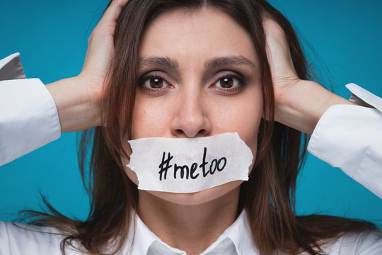 Closeup portrait of young woman in fright clings to her head with her hands, the mouth is sealed with a white plaster with the inscriptionon  #metoo blue background. #metoo movement concept.