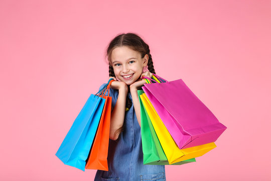 Young girl in denim dress with shopping bags on pink background