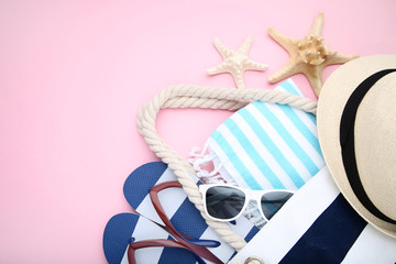 Summer bag with flip flops and starfishes on pink background