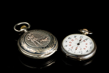 Two old pocket watches on a black reflective surface