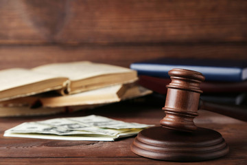 Judge gavel with dollars and books on wooden table