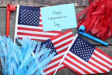American flags and paper with inscription Happy Independence Day on wooden table