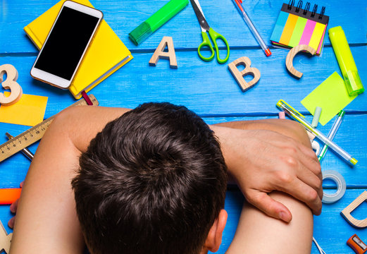 A student is asleep in the workplace, a creative mess. The student is lazy and does not want to learn. The guy is tired and asleep on the table. The concept of education and learning process. Lessons
