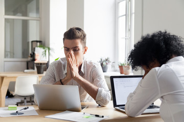 Upset millennial workers feeling despair witnessing company crisis online, stressed colleagues disappointed reading bankruptcy news at laptop, depressed businesspeople losing money on stock