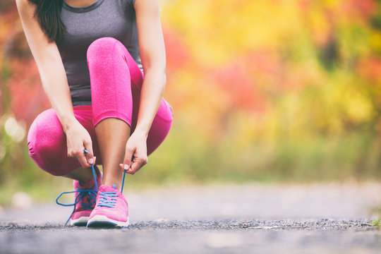 Runner tying running shoes laces in autumn background. Athlete woman getting ready to run race in fall landscape with yellow leaves foliage in park.