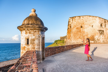Old San Juan city tourist taking photo in Puerto Rico. Woman using phone taking pictures of ruins of watch tower of San Cristobal Castillo Fort, with ocean background.