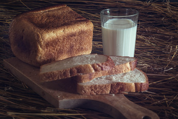 Healthy food. Long loaf of rural bread with two cut-off pieces lie on a wooden chopping board and a glass of fresh milk. Dark background. Horizontal shot