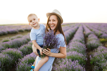 Young woman in blue dress hat walk on purple lavender flower meadow field background, rest, have fun, play with little cute child baby boy. Mother small kid son. Family day, parents, children concept.