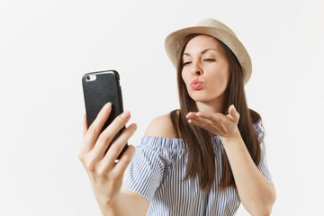 Young woman in blue dress, hat blowing kisses, doing selfie shot on mobile phone or video call isolated on white background. People, sincere emotions, lifestyle concept. Advertising area. Copy space.