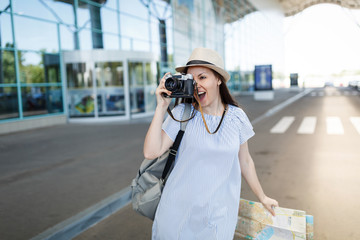 Young traveler tourist woman with backpack holding retro vintage photo camera, paper map at international airport. Female passenger traveling abroad to travel on weekends getaway. Air flight concept.