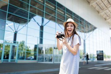 Young surprised joyful traveler tourist woman in hat holding retro vintage photo camera at international airport. Female passenger traveling abroad to travel on weekends getaway. Air flight concept.