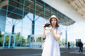 Young shocked traveler tourist woman in hat with backpack hold retro vintage photo camera at international airport. Female passenger traveling abroad to travel on weekends getaway. Air flight concept.