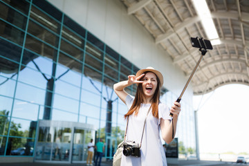 Traveler tourist woman with retro vintage photo camera show victory sign, doing selfie on mobile phone with monopod selfish stick at airport. Passenger traveling abroad on weekend. Air flight concept.