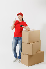 Full length portrait of delivery woman in red cap, t-shirt isolated on white background. Female courier near empty cardboard boxes with credit card. Receiving package. Copy space for advertisement.