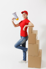 Full length of delivery fun woman in red cap, t-shirt isolated on white background. Female courier screaming in megaphone hot news, standing near empty cardboard boxes. Receiving package. Copy space.