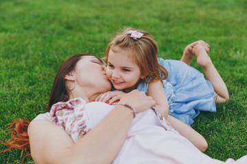 Tender woman in light dress kissing little cute child baby girl lie on green grass in park rest and have fun. Mother, little kid daughter. Mother's Day, love family, parenthood, childhood concept.