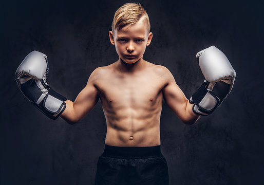 Young shirtless boy boxer with boxing gloves posing in a studio. Isolated on dark textured background.
