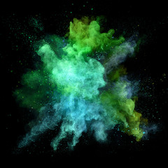 Explosion of coloured powder on black background