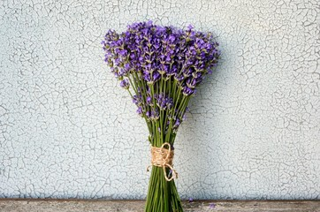 Bouquet of lavender on an old wooden table on a cracked white background.