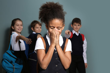 Children bullying African-American girl on color background