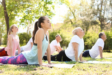 Group of people practicing yoga in park on sunny day Fotomurales