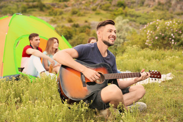 Man playing guitar near camping tent in wilderness