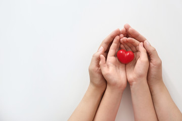 Young woman and child holding red heart on light background, top view