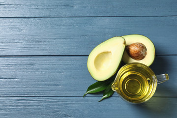 Gravy boat with oil and ripe fresh avocado on wooden table, top view