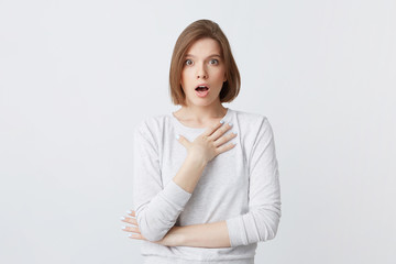 Amazed lovely young woman in longsleeve standing with opened mouth and hands folded isolated over white background Feels shocked