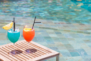 two perfect orange and blue exotic cocktails on the table, pool background