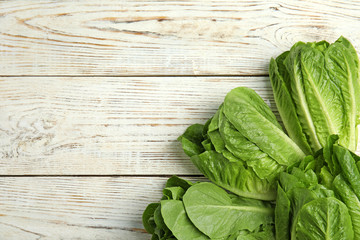 Fresh ripe cos lettuce on wooden background, top view