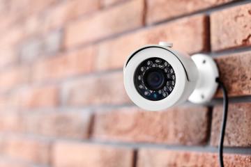 Modern security CCTV camera on brick wall