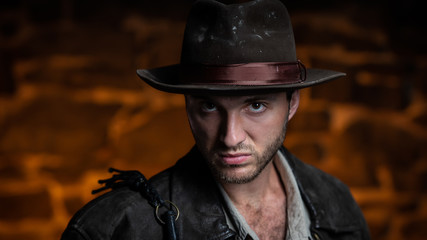 adventurer (Indiana Jones). stone wall background.