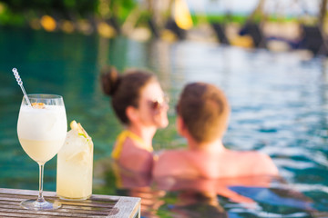 young pretty couple enjoing summer evening with cocktails in luxury pool